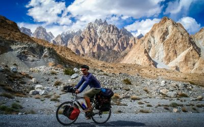 Solo male cyclist on the stunning road through Karakorum mountains in Pakistan, with Tupopdam peak in the background, Passu area